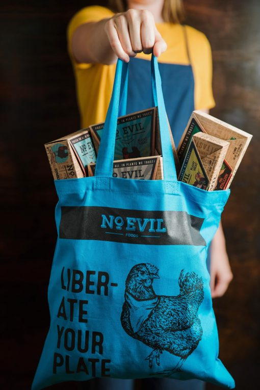 "Blue tote bag with No Evil Foods logo and chicken image, text reads, ""Liberate Your Plate"""