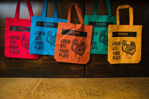 """Group of colored tote bags with No Evil Foods logo and chicken image, text reads, """"Liberate Your Plate"""""""