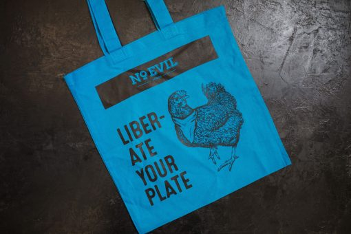 """Blue tote bag with No Evil Foods logo and chicken image, text reads, """"Liberate Your Plate"""""""