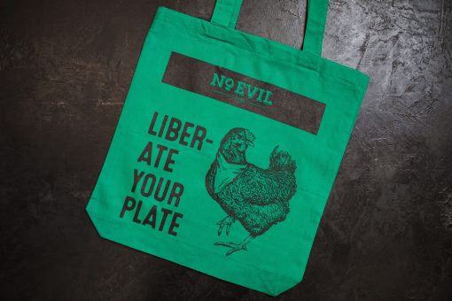 "Green tote bag with No Evil Foods logo and chicken image, text reads, ""Liberate Your Plate"""