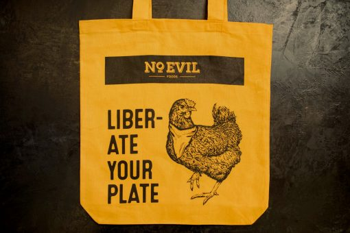 """Gold tote bag with No Evil Foods logo and chicken image, text reads, """"Liberate Your Plate"""""""