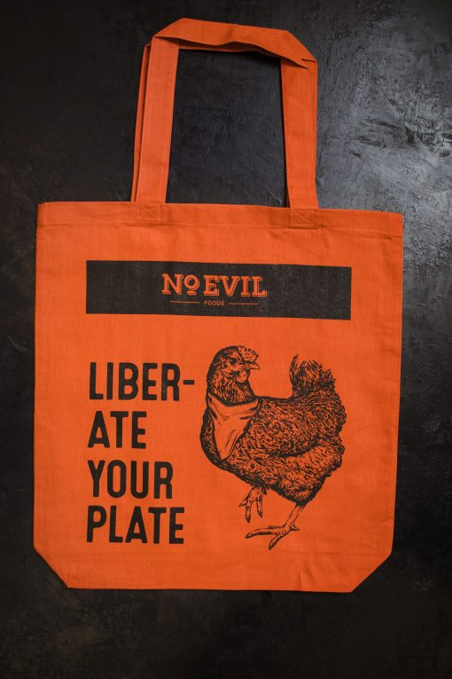 "Orange tote bag with No Evil Foods logo and chicken image, text reads, ""Liberate Your Plate"""