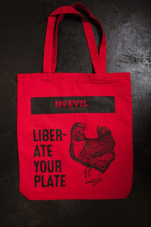 "Red tote bag with No Evil Foods logo and chicken image, text reads, ""Liberate Your Plate"""