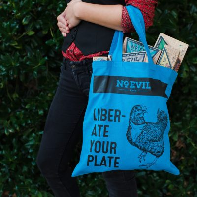 """Blue tote bag filled with vegan meat with No Evil Foods logo and chicken image, text reads, """"Liberate Your Plate"""""""
