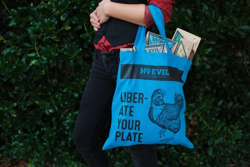 "Blue tote bag filled with vegan meat with No Evil Foods logo and chicken image, text reads, ""Liberate Your Plate"""